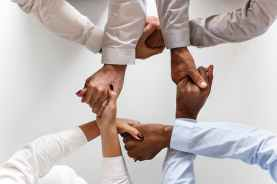 photo of four persons uniting hands