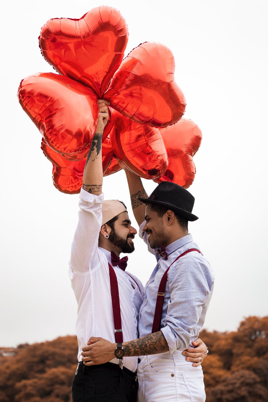 two men holding red heart balloons